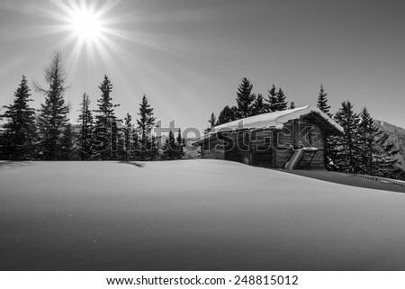 Mountain sun over the ski hut in black and white - stock photo
