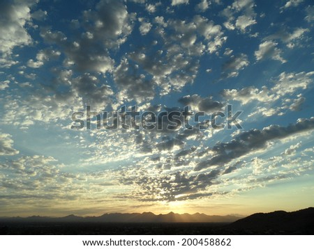 Mountain sunrise with layer of spotted clouds - stock photo