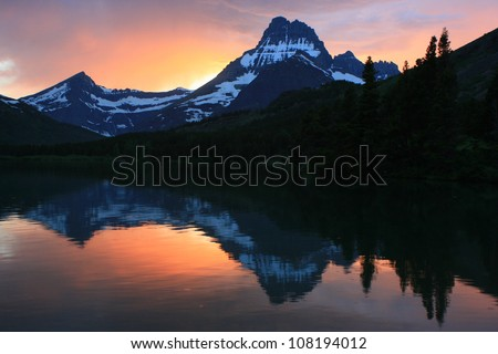 Mountain sunset on Swiftcurrent Lake in the Many Glacier region of Glacier National Park, Montana - stock photo