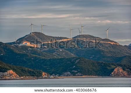 Mountain top row of wind turbines on China's Jintang Island in Zhejiang Province - stock photo