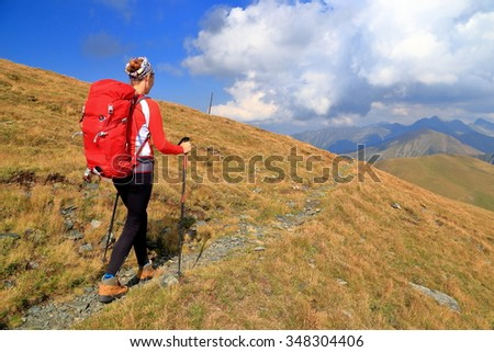 Mountain trail and woman hiker carrying a red backpack - stock photo