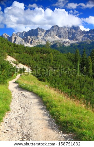 Mountain trail, green meadow and distant mountains, Dolomite Alps, Italy - stock photo
