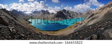Mountain turquoise Alakol lake in Kyrgyzstan, Tian Shan panorama - stock photo