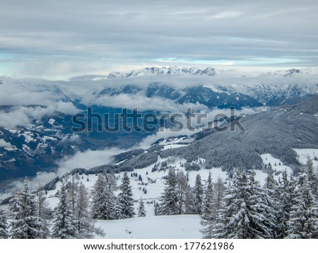 Mountain valley at winter covered with snow and clouds - stock photo