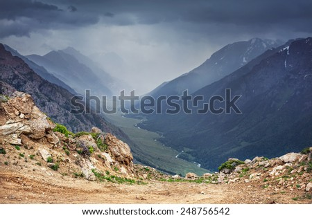 Mountain valley with river and overcast grey sky in Dzungarian Alatau Kazakhstan, Central Asia - stock photo