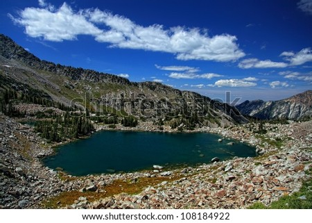 Mountain view from way up above a mountain lake surrounded by huge boulders with a view down toward Salt Lake City Utah under partly cloudy sky's/ Upper Red Pine Lake - stock photo