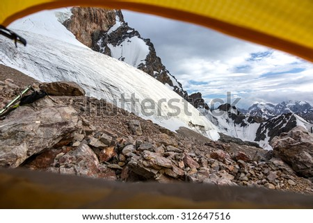 Mountain View from Yellow Tent. Landscape from Camping Tent Vanishing Point Steep Glacier Tongue  Ice and Rock Cliff Terrain Alpine Gear - stock photo