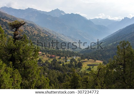 Mountain view with village and forest View of mountain perspective with several ranges with back-light sunrise and small settlement on foreground