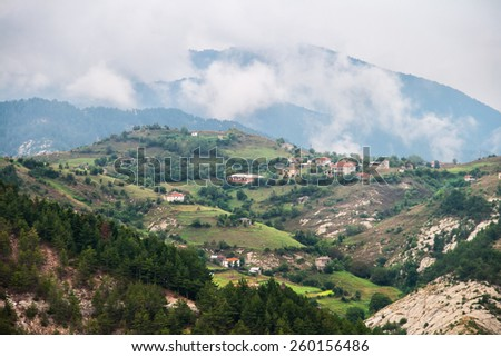 Mountain village on a slope and cloudy sky - stock photo