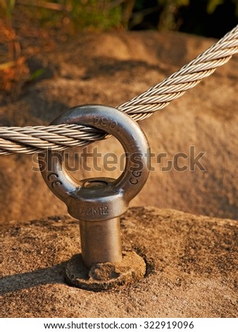 Mountain wall with chrome bolt eye in the rock. The iron rope in loop. - stock photo
