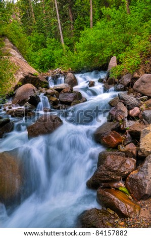 Mountain Waterfall - blue water and huge boulders surrounded by green trees - stock photo