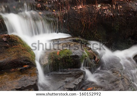 Mountain waterfall, cascading by rocks, a relaxing place for travelers