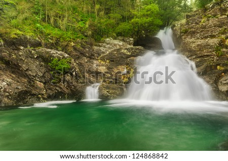 Mountain waterfall, stream of water in forest and mountain terrain. - stock photo