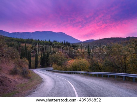 Mountain winding road passing through the forest with dramatic colorful sky and red clouds at dusk in summer. Mountain landscape - stock photo