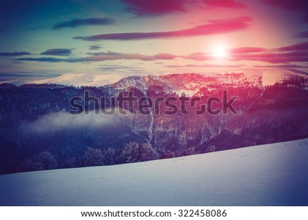 Mountain winter landscape. Fantastic evening glowing by sunlight. Retro filter. Filtered image: instagram toning effect. Happy New Year! - stock photo