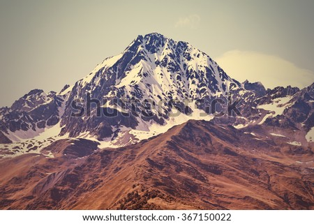 Mountain with instagram filter effect. Peak in snow and brown grass below. - stock photo