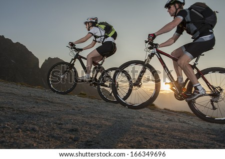 mountainbike - two bikers by uphill mountainbiking on sunset - sunrise