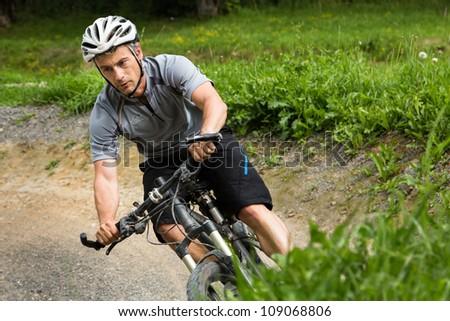 Mountainbiker driving through a curve - stock photo