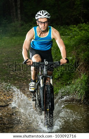 mountainbiker driving through a streambed - stock photo