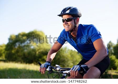 Mountainbiker riding bike in countryside - stock photo