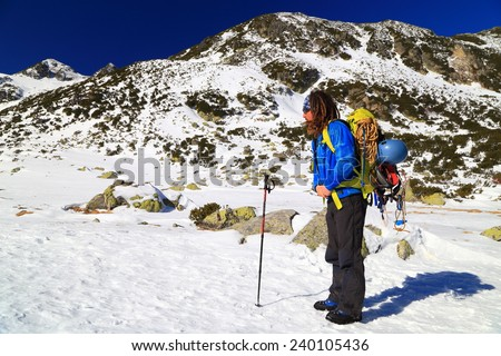 Mountaineer adjusting backpack while standing on snow covered mountain - stock photo