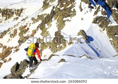 Mountaineer ascending on snow covered mountain ridge - stock photo