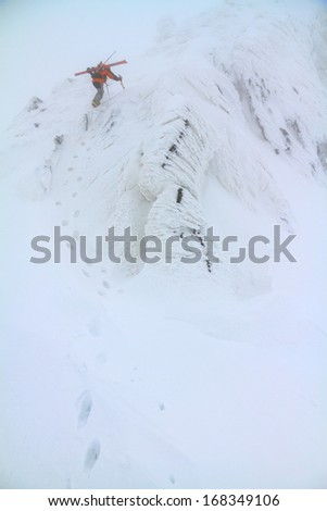 Mountaineer ascending snowy slope in bad weather - stock photo