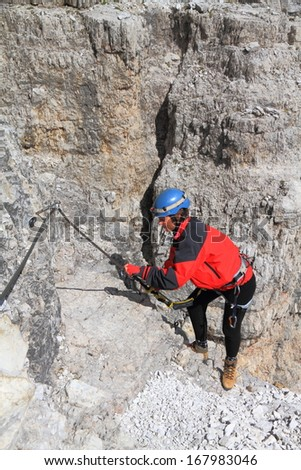 Mountaineer ascending via ferrata cable, Dolomite Alps, Italy