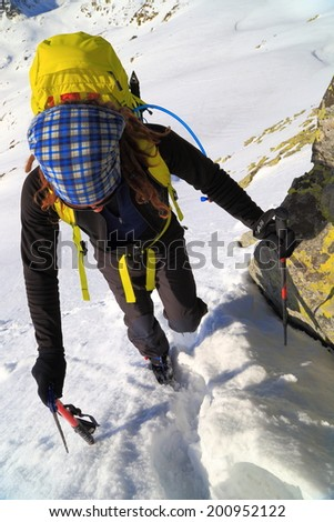 Mountaineer ascends snow covered gully in sunny day