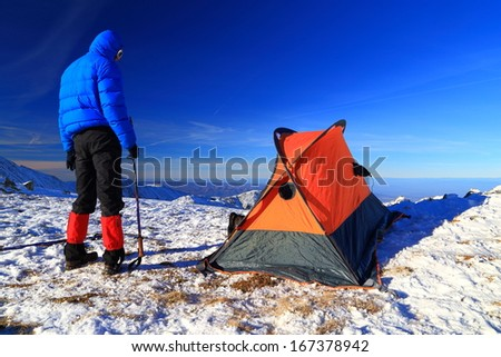 Mountaineer camping on snowy mountain - stock photo