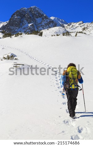 Mountaineer carries climbing gear while following foot steps on a white snow field - stock photo