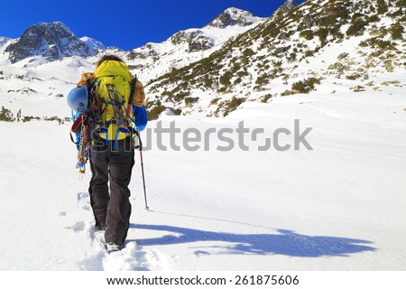 Mountaineer carries heavy backpack and climbing gear in sunny winter day - stock photo