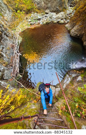 Mountaineer climbing a rusty iron ladder on a mountain