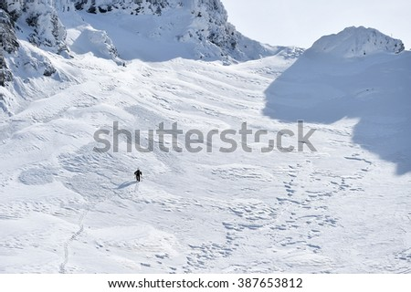 Mountaineer climbing with crampons on alpine valley in Fagaras Mountains in Romania
