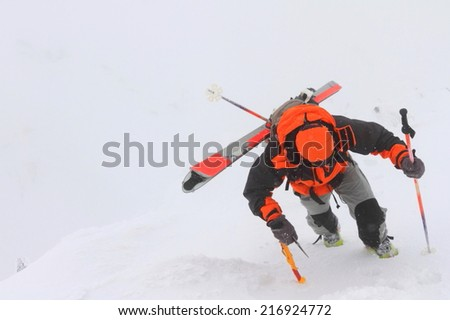 Mountaineer climbs an icy slope in adverse weather - stock photo