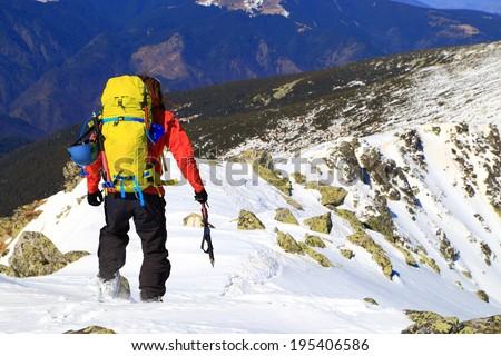 Mountaineer descends a snowy ridge in winter - stock photo