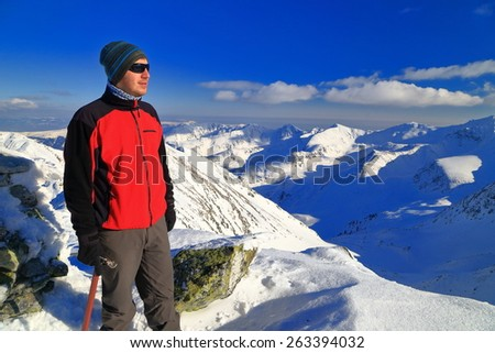 Mountaineer enjoying the view from the mountain top in sunny winter day - stock photo