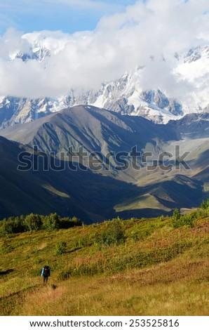 Mountaineer following famous trekking route to Ushguli village, Georgia, Caucasus mountains,Upper Svaneti,Central Asia - stock photo