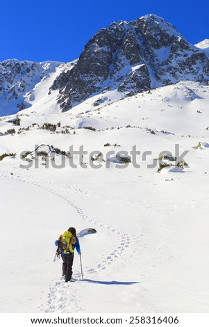 Mountaineer follows a snow covered plateau in winter - stock photo