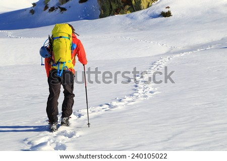 Mountaineer follows a trail of foot steps on snowy mountain  - stock photo