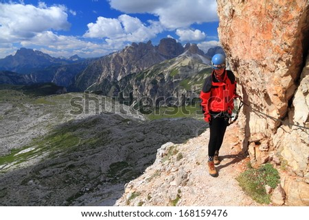 Mountaineer follows the steel cable of via ferrata, Dolomite Alps, Italy