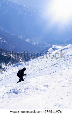 Mountaineer goes to the top of a snowy mountain in a sunny winter day - stock photo