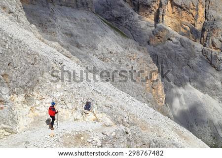 Mountaineer on descending path towards Gardeccia valley, Dolomite Alps, Italy - stock photo