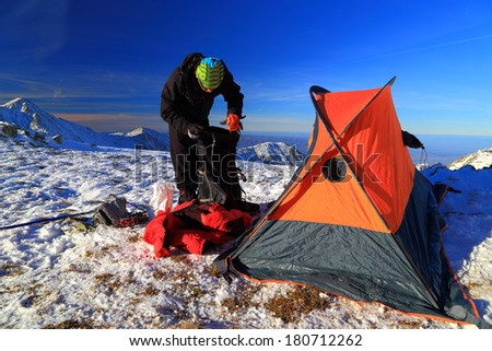 Mountaineer prepares the tent in winter
