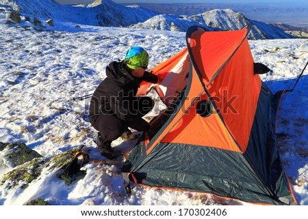 Mountaineer preparing an orange tent to camp on snowy mountain