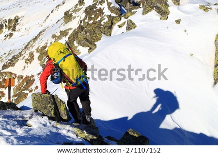 Mountaineer preparing to descend snow covered ridge in sunny day of winter  - stock photo