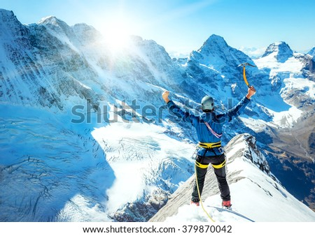Mountaineer reaches the top of a snowy mountain. Extreme sport concept - stock photo