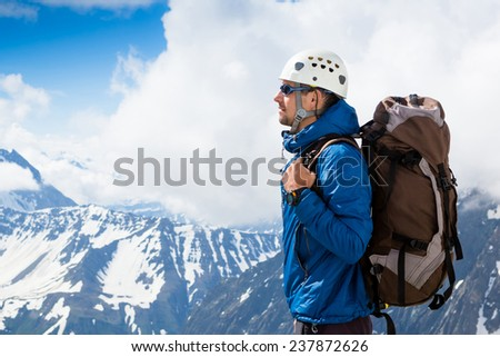 Mountaineer reaches the top of a snowy mountain in a sunny day. Alp - stock photo