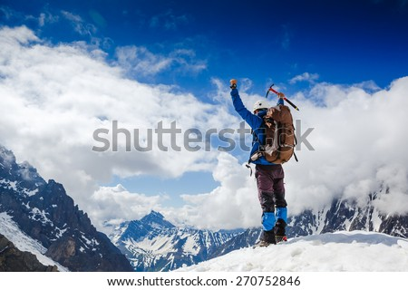Mountaineer reaches the top of a snowy mountain in a sunny winter day - stock photo