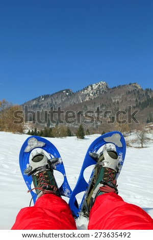 Mountaineer's legs with snowshoes for excursions in the mountains - stock photo